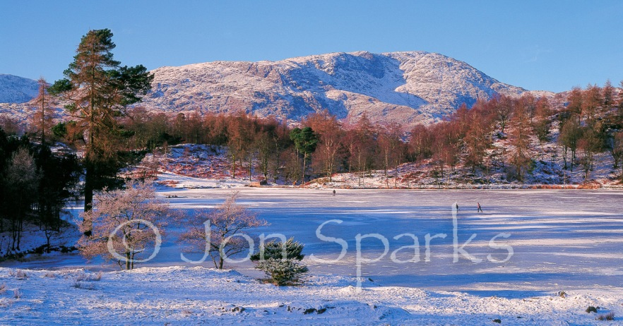 Skaters on Tarn Hows, with Wetherlam behind. Not the model for the tarn in the book, but skating photos are rare!